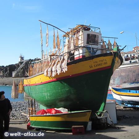 Fischerboote am Hafen von Câmara de Lobos, Stockfisch trocknet an Holzgestellen in der Sonne
