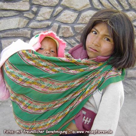 Indiomädchen in Chivay mit kleiner Schwester im TragetuchFoto:© www.reisepfarrer.de