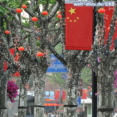Red flags, lanterns and lights decorate the trees