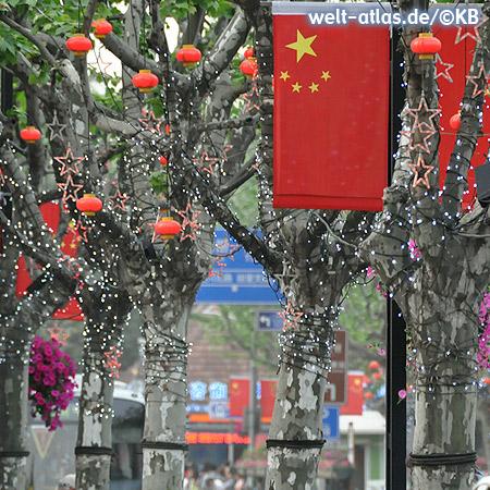 Rote Fahnen, Lampions und Lichter schmücken die Bäume