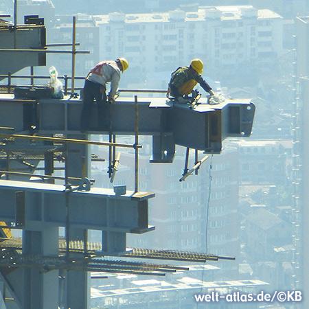 Bauarbeiter in luftiger Höhe auf einem Wolkenkratzer in Shanghai