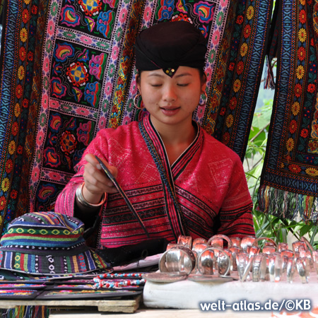Yao woman in traditional red costume, in the background you can see the beautiful textiles and typical patterns