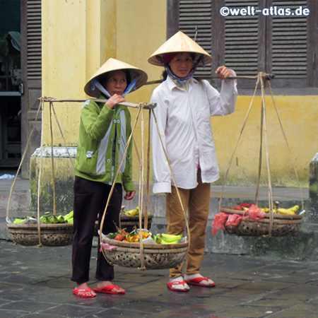 Zwei Frauen mit den typischen Hüten verkaufen exotische Früchte