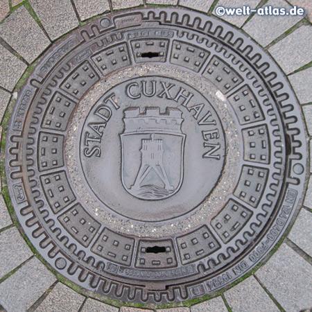 Kanaldeckel aus Cuxhaven mit dem Wahrzeichen der Stadt, der Kugelbake im Wappen