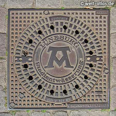 """manhole cover in Lüneburg with symbol for the motto """"Mons, Pons, Fons"""" (""""Hill, bridge, spring"""")"""