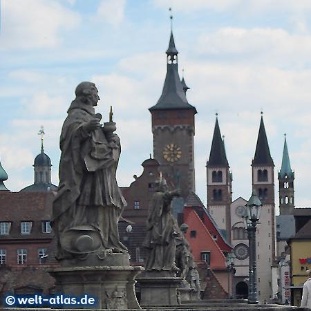 Brückenheilige auf der alten Mainbrücke in Würzburg, dahinter die Türmen von Rathaus und Dom