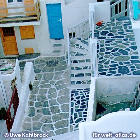 Stairs, colored balconies and patterns of street pavement in the picturesque lanes of Mykonos Town