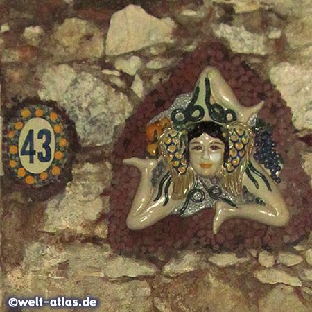 """Trinacria, Siziliens Symbol bedeutet """"die drei Vorgebirge"""", hier am schön verzierten Haus mit bemalter Tür, sizilianischen Fliesen und viel weiterem Fassadenschmuck, Taormina Altstadt"""
