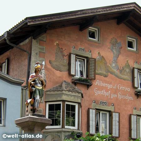Gasthof mit wunderschöner Fassade am Tinneplatz im historischen Zentrum des mittelalterlichen Ortes Klausen im Eisacktal bei Brixen, davor der Brunnen mit St. Florian