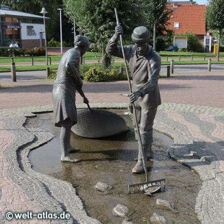 """Die Bronzeskulptur """"Jan und Gret"""" auf dem Marktplatz im Dorf – Gret sammelt Krebse, Muscheln und Aale und Jan sticht den Plattfisch – St. Peter-Ording"""