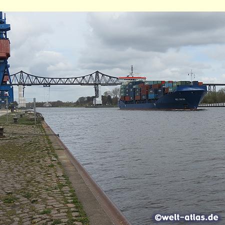 Kaianlagen und Containerschiff am Nord-Ostsee-Kanal mit Rendsburger Eisenbahnhochbrücke und Schwebefähre