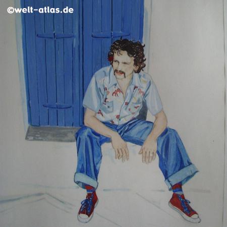 Auf Aegina, junger Mann vor blauer Tür sitzend, in Aghia Marina