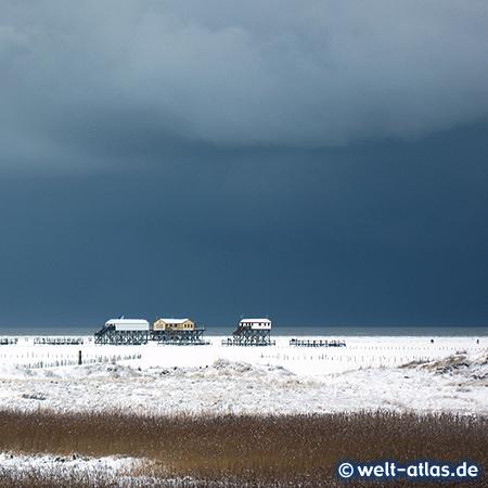 Dramatischer Himmel und Wolkenbildung im Winter in St. Peter-Ording, Bilck über das Vorland und den Strand auf die Pfahlbauten am Meer