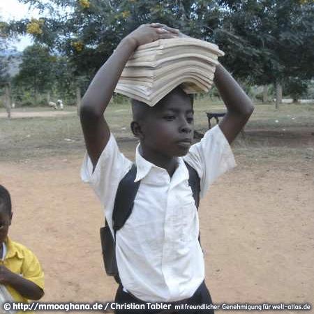 Junge auf dem Weg zur Schule, seine Hefte werden auf dem Kopf transportiert. (Hilfe für Ghana, http://mmoaghana.de)