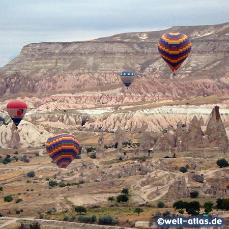 Heissluftballons vor der rosafarbenen Felswand des Aktepe