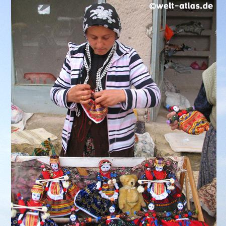 Frau beim Nähen einer Soganli-Puppe, in der Tracht der Region