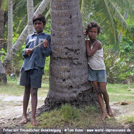 Zwei Kinder lehnen an einer Palme