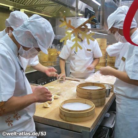 Köche bereiten Dim Sum, die in Bambuskörben gegart werden