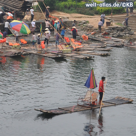 Bamboo rafts with beach umbrellas and deckchairs on Li River