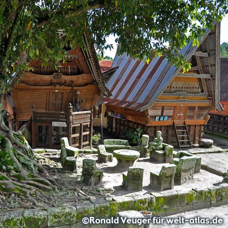 Batak-Häuser, steinerne Gerichtsstühle und Tische im Batak-Dorf Ambarita auf der Insel Samosir im Tobasee (Ambarita Stone Chair Village)