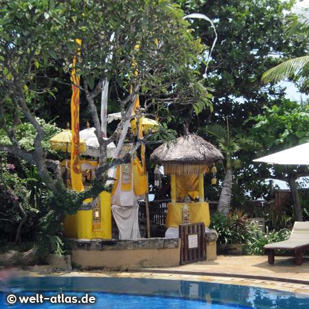 Hotelpool unter Bäumen mit einem Tempel direkt daneben