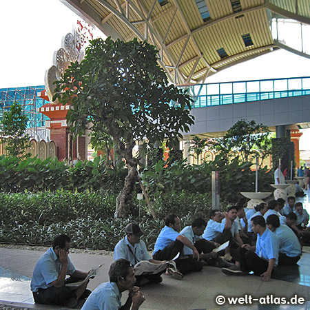 Arrival at the airport in Denpasar, airport workers are relaxing in front of the terminal building