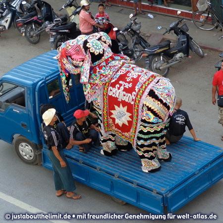 """In Pyin U Lwin, tanzende """"Elefanten"""" auf einem LKW, Figuren aus Papier und Textilien mit zwei Personen darunter"""