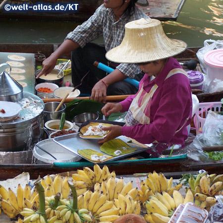 Frau im Boot mit ihrer Garküche auf dem Schwimmender Markt bei Damnoen Saduak, Provinz Ratchaburi