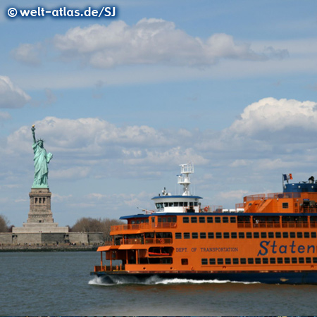 Die Freiheitsstatue auf Liberty Island und eine Staten Island Ferry im New Yorker Hafen